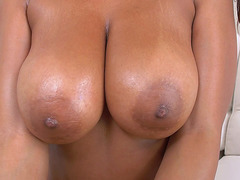 Black chick Katt Garcia is pushing her tits together.