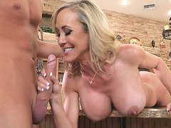 Brandi Love gives the hot blowjob lying on the table